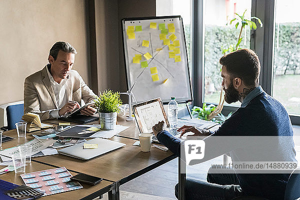 Geschäftsleute  die im Büro mit einem digitalen Tablet und Laptop arbeiten