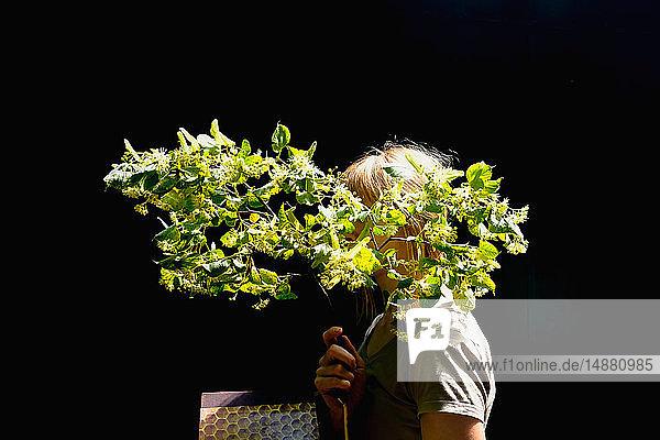 Frau hält Zweig einer grünen Frühlingsblüte vor dem Gesicht