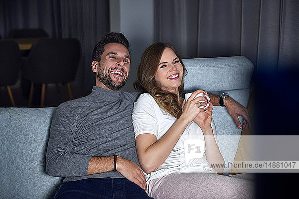 Young couple sitting on sofa in evening  laughing while watching TV