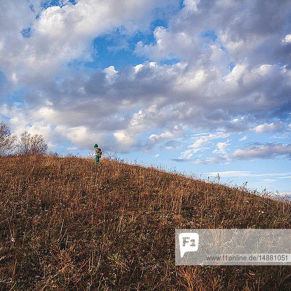 Boy on rural hillside looking down