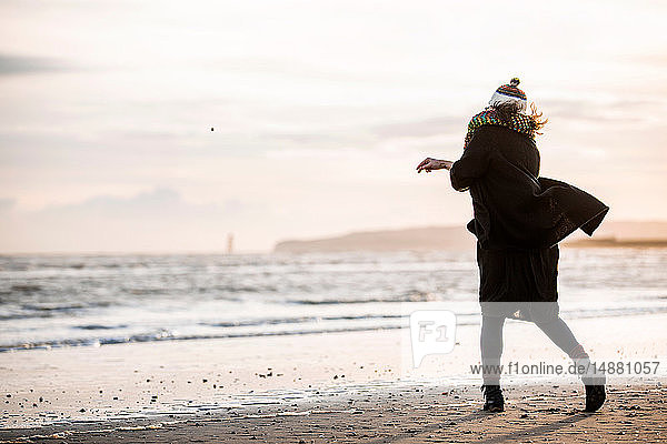 Woman throwing pebbles on beach