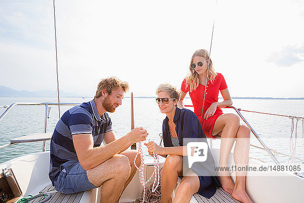 Young man and adult women tying rope knots on sailboat on Chiemsee lake  Bavaria  Germany