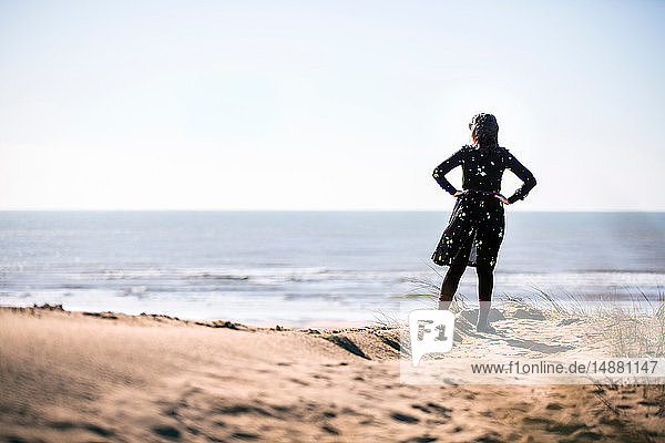 Woman looking out to sea on beach