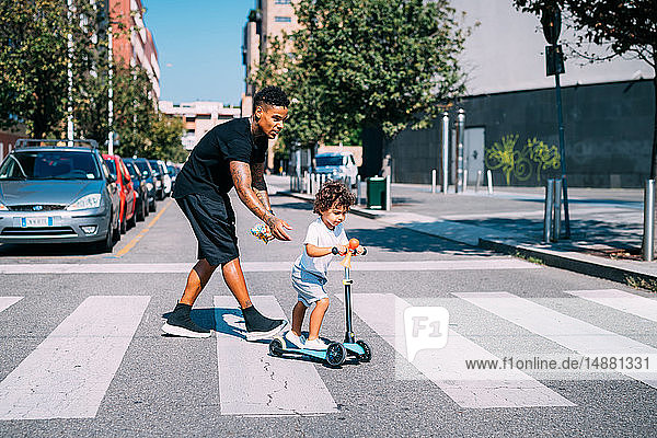 Father helping son ride push scooter on pedestrian crossing