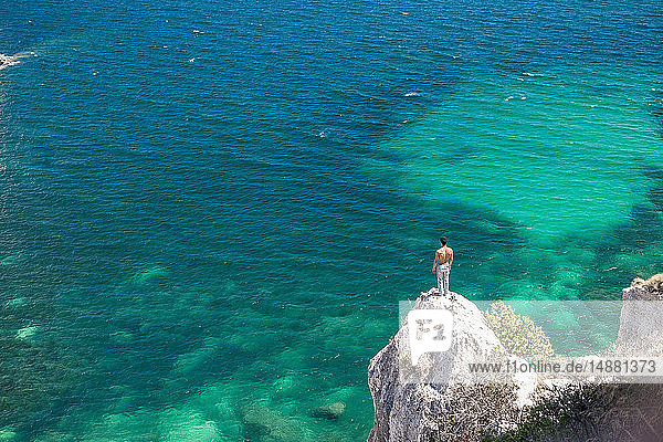 Young man looking out from coastal rock  Cagliari  Sardinia  Italy