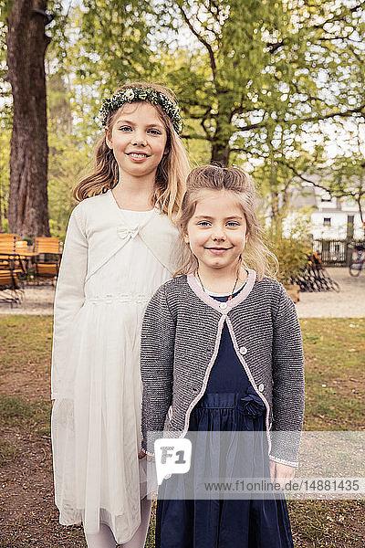 Mädchen mit Blumenkopfbedeckung im Park mit Schwester  Porträt