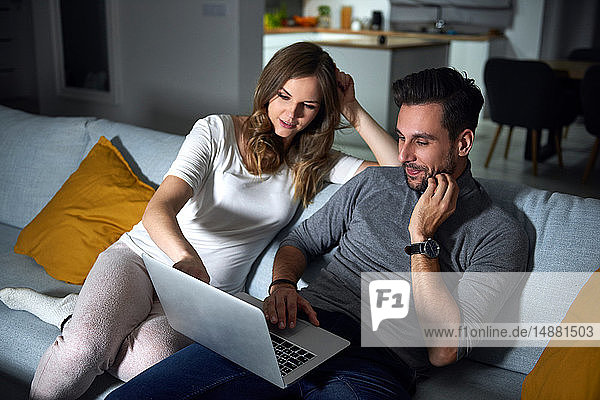 Young couple sitting on sofa in evening looking at laptop