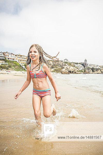 Girl wearing bikini running in sea  Los Angeles  California  USA