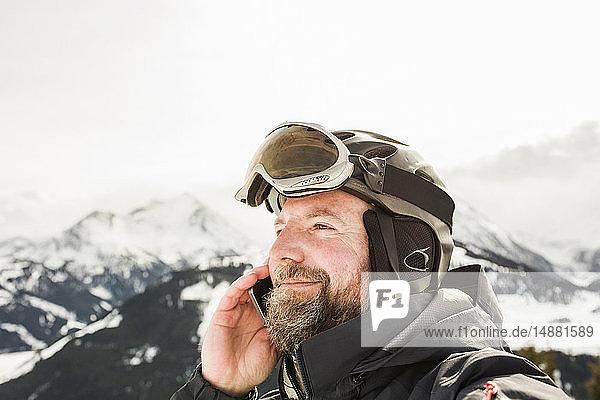 Älterer Skifahrer telefoniert mit seinem Smartphone auf schneebedecktem Berg  Gerlos  Tirol  Österreich