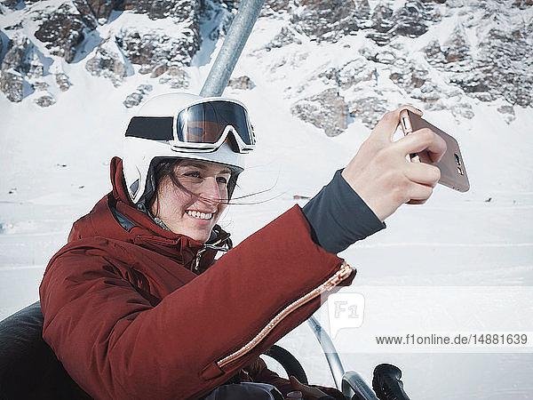 Junge Skifahrerin mit Helm und Skibrille  die mit Selfie auf Skilift fährt  Alpe Ciamporino  Piemont  Italien