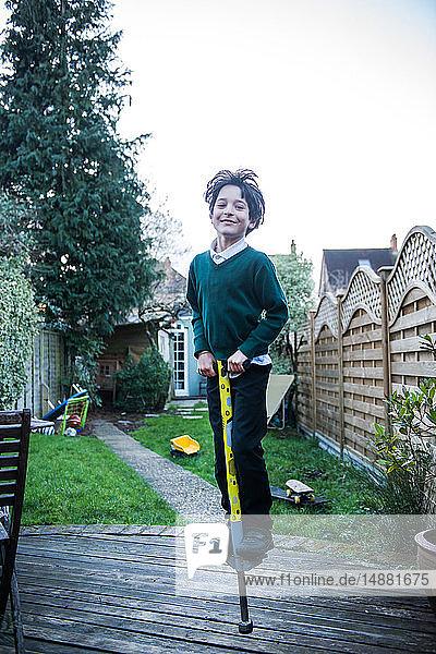 Junge springt auf Pogo-Stock im Garten