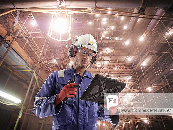 Zusammengesetztes Bild eines Ingenieurs im Kraftwerk während eines Ausfalls mit Hilfe eines digitalen Tablets