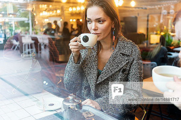 Young woman drinking coffee with friend in cafe,  London,  UK