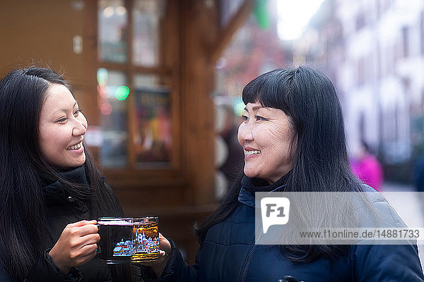 Mother and daughter drinking at Christmas market  Freiburg  Baden-Wurttemberg  Germany