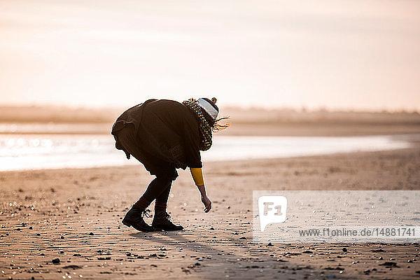 Frau sammelt Kieselsteine am Strand
