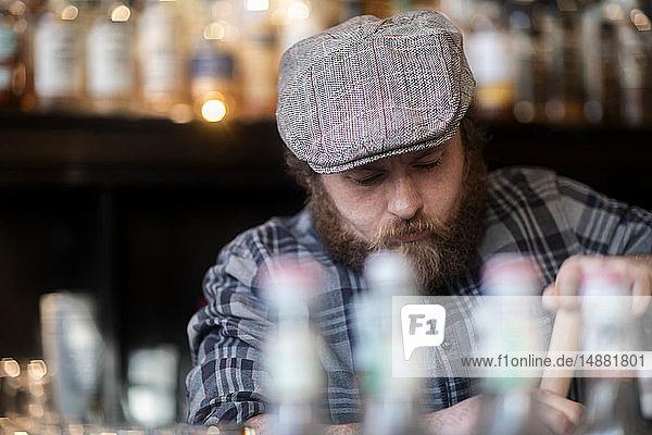 Barman working behind bar in traditional Irish public house