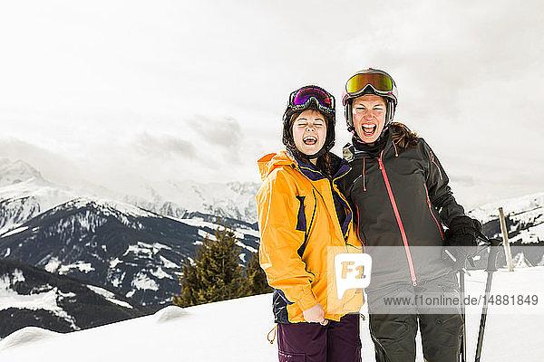 Zwei lachende Skiläuferinnen auf schneebedecktem Berg,  Gerlos,  Tirol,  Österreich