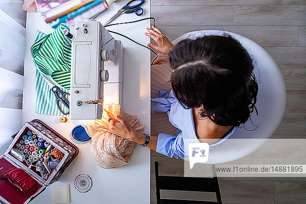 Woman using sewing machine beside window