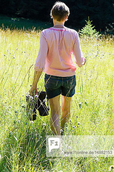 Frau pflückt Wildblumen im Wald