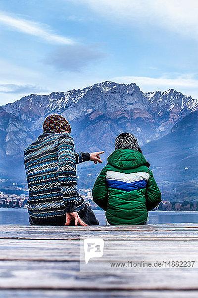 Junge und Vater sitzen auf der Seebrücke  Rückansicht  Comer See  Onno  Lombardei  Italien