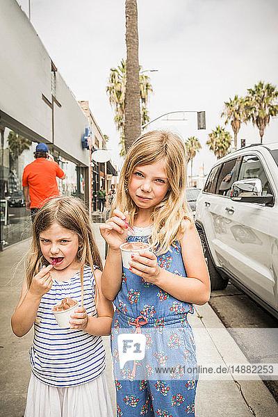 Mädchen und Schwester essen Eiscreme auf dem Bürgersteig  Porträt  Los Angeles  USA