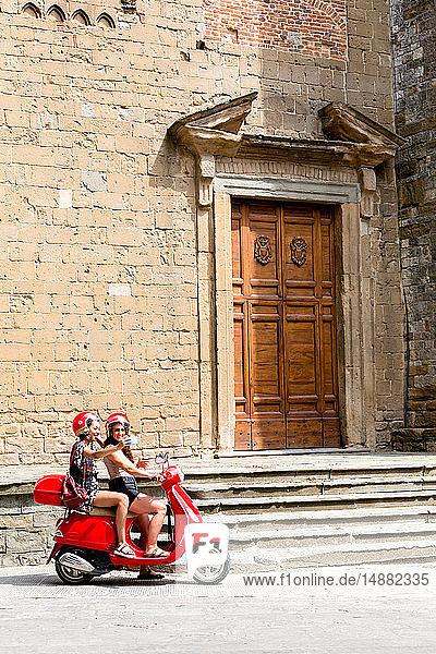 Freunde  die sich auf dem Roller durch den Eingang der Kirche selbst auf dem Roller mitnehmen  Città della Pieve  Umbrien  Italien