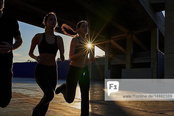 Freunde joggen bei Sonnenuntergang im Sportstadion
