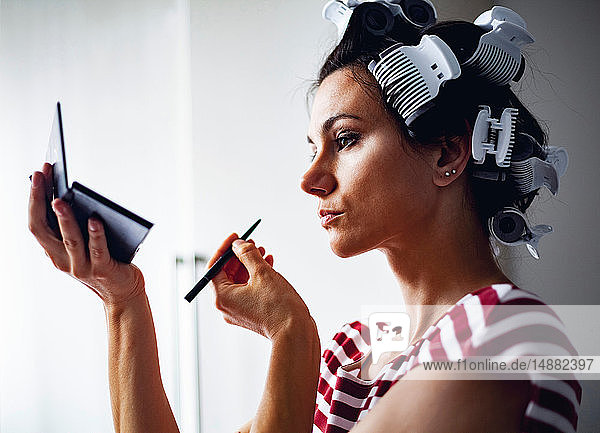 Woman with hair-rollers putting on make up
