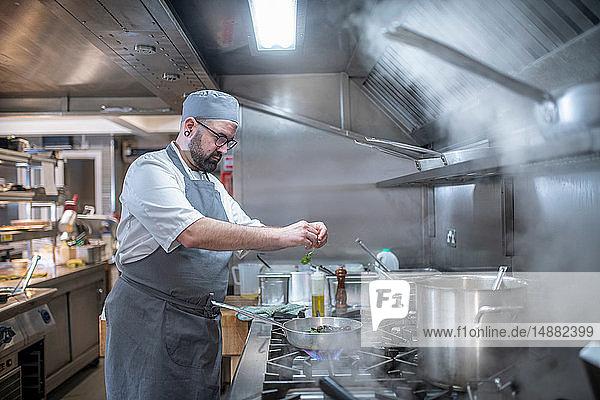 Küchenchef legt in italienischer Restaurantküche Kräuter in die Pfanne