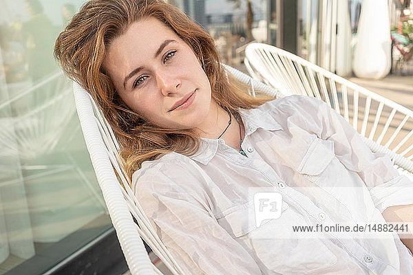 Junge Frau entspannt sich auf einem Stuhl im Freien