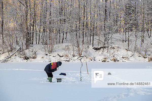 Landscape with man fishing on snow covered frozen lake