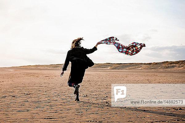 Frau rennt mit Stranddecke