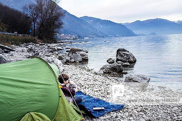 Junge sitzt auf einer Decke am Zelt und trinkt Kaffee am Seeufer  Comer See  Onno  Lombardei  Italien
