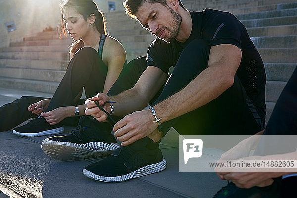 Freunde binden Schnürsenkel an Stufen im Sportstadion