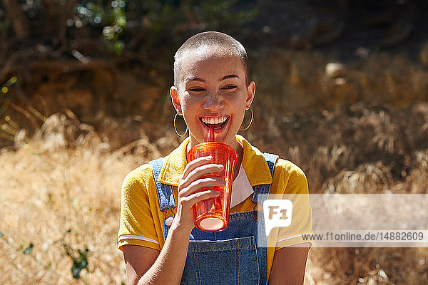 Teenage girl with cropped hair drinking from takeaway cup in park  Los Angeles  California  USA