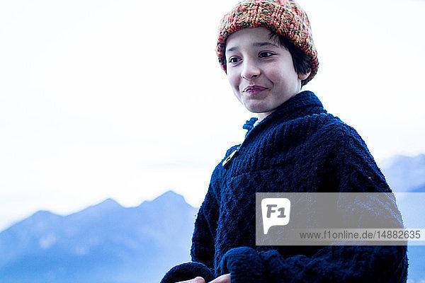 Porträt eines Jungen in Winterwollen  im Hintergrund Gebirge