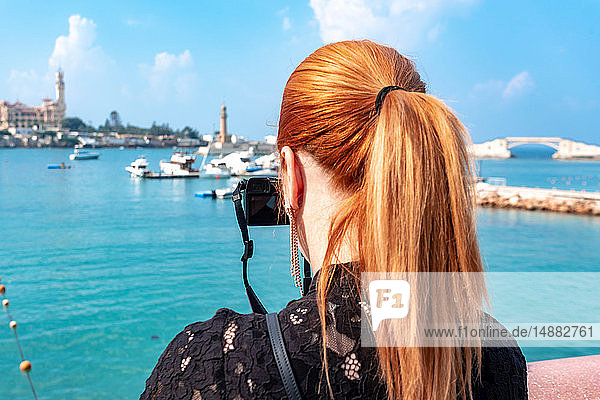 Female tourist with red hair photographing over sea toward Montaza palace  rear view  Alexandria  Egypt