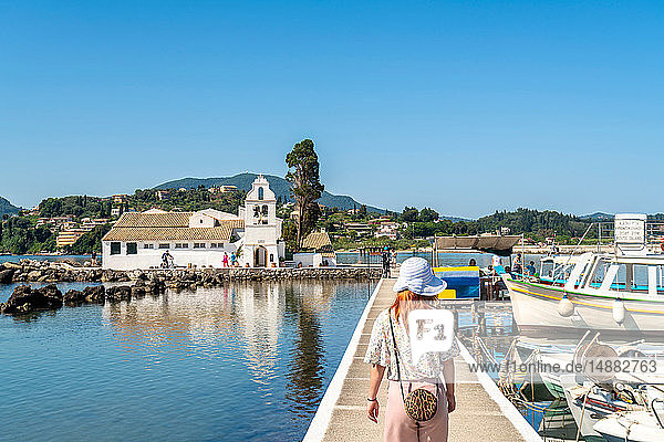 Tourist walking on bridge leading to Vlacherna Monastery  island on background  Corfu  Kerkira  Greece