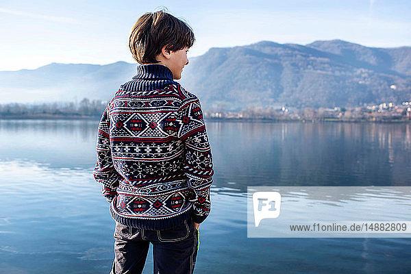 Junge schaut vom Seeufer aus  Rückansicht  Comer See  Lecco  Lombardei  Italien