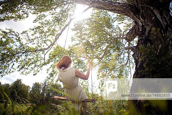 Frau auf Schaukel im Wald