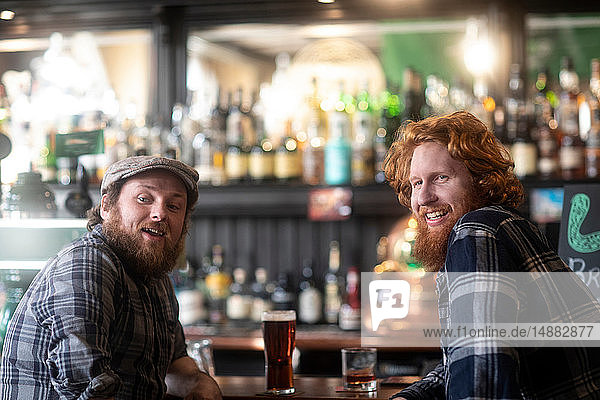 Two male customers looking over their shoulders from bar in traditional Irish public house