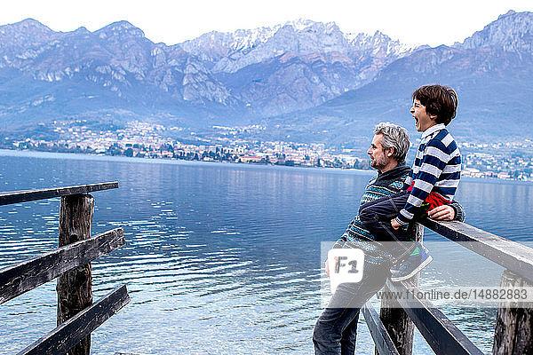 Junge und Vater schauen von der Seebrücke aus  Comer See  Onno  Lombardei  Italien