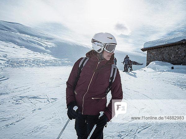 Junge Skifahrerin mit Helm und Skibrille beim Blick zurück in die verschneite Landschaft  Alpe Ciamporino  Piemont  Italien
