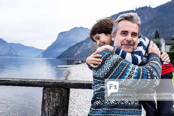 Junge und Vater umarmen sich am Pier des Comer Sees  Comer See  Onno  Lombardei  Italien
