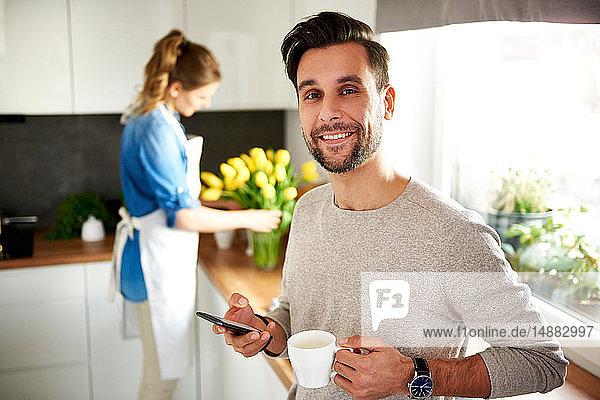 Mann benutzt Smartphone in der Küche  Frau arrangiert Blumen im Hintergrund