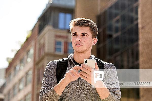 Junger Mann nutzt Smartphone und erkundet Stadt  London  UK