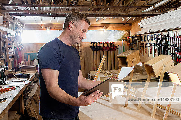 Designer using digital tablet by prototypes of table lamps