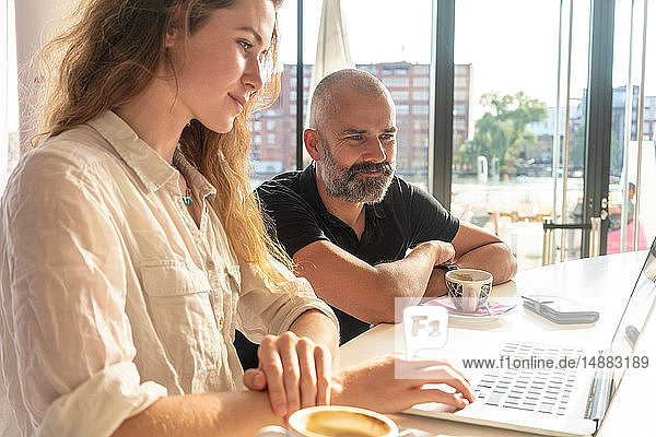 Two entrepreneurs using laptop and having coffee in office