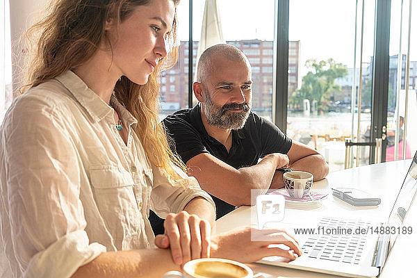 Zwei Unternehmer mit Laptop und Kaffee im Büro