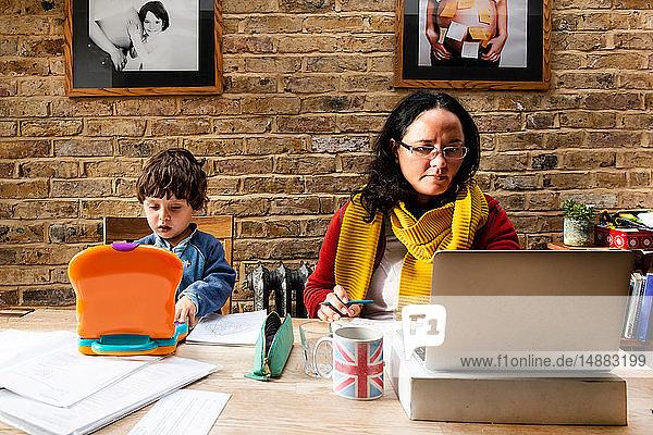 Kleinkind Junge lernt von Mutter  die von zu Hause aus arbeitet